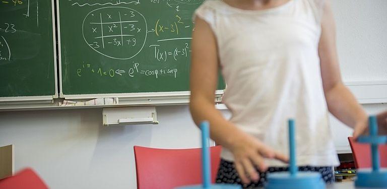 Ein Kind spielt mit mathematischen Objekten vor einer Tafel mit mathematischen Rechnungen.