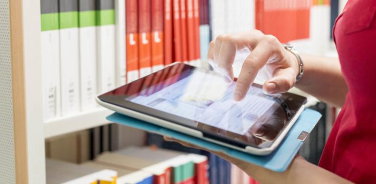 Frau mit Tablet in einer Bibliothek; Bild zum Projekt SINIR