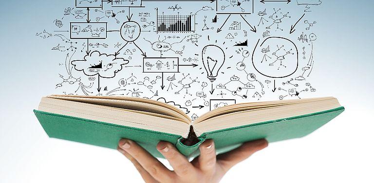 Bild von einem aufgeschlagenen Buch, das auf einer Hand liegt. Darüber sind Diagramme und Zeichen zu sehen, die miteinander verknüpft sind.
