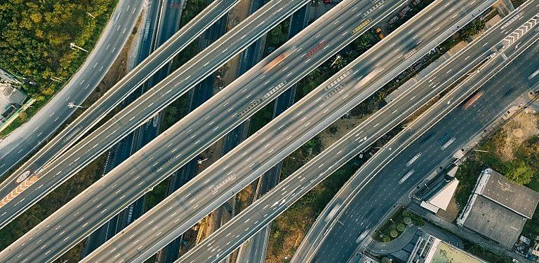 Ein kompliziertes Autobahnkreuz von oben. Viele Straßen, die übereinander verlaufen.